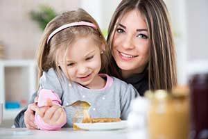 Mutter und Kind frühstücken mit Manuka Honig